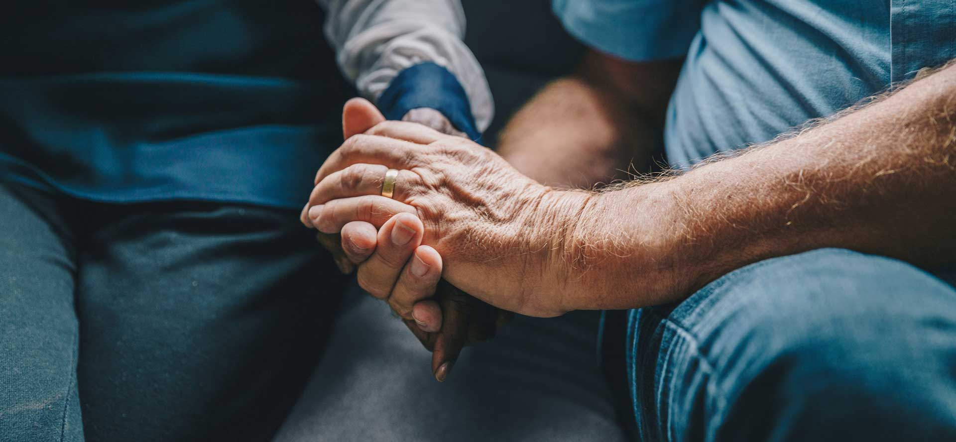 older man's hand holding woman's hand on couch